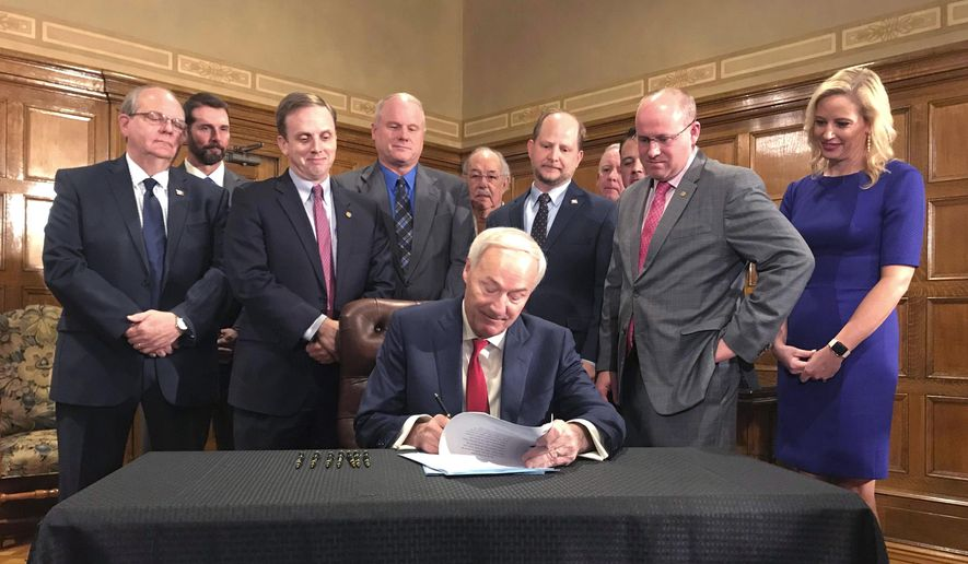 Arkansas Gov. Asa Hutchinson, seated, signs a highway funding bill on Tuesday, March 12, 2019 at the state Capitol in Little Rock, Ark. The legislation raises fuel taxes and taps into expected casino revenue to pay for roads. (AP Photo/Andrew DeMillo)