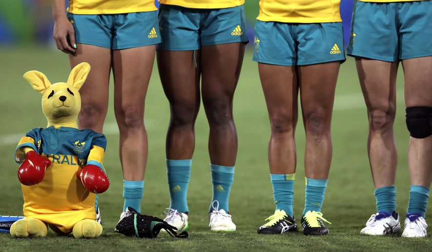 FILE- In this Aug. 8, 2016, file photo, Australia's players are accompanied by a boxing kangaroo mascot as they line up for the singing of the national anthem during the women's rugby sevens gold medal match at the Summer Olympics in Rio de Janeiro, Brazil. Led by girls and young women, the ruck-and-maul and rougher-than-rough sport of rugby union is looking to regain its relevance in Australia. (AP Photo/Themba Hadebe, File)
