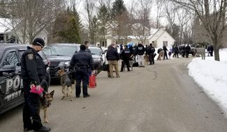 In this March 9, 2019 photo provided by the Hartford Police Department, several K9 law enforcement officers and their dogs arrive at the home of Emma Mertens in Hartford, Wis. The 7-year-old Wisconsin girl, a lover of dogs who is suffering from a potentially fatal brain tumor, got a boost of support when the officers and K9s arrived at her home. A family friend had posted a request on social media for people to send photos of their dogs. Emma's family says she has since received thousands of letters and photos from around the world.  (Hartford Police Department via AP)
