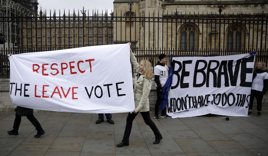"Pro-Brexit leave the European Union supporters, left, and anti-Brexit remain in the European Union supporters take part in a protest outside the Houses of Parliament in London, Tuesday, March 12, 2019. British Prime Minister Theresa May faced continued opposition to her European Union divorce deal Tuesday despite announcing what she described as ""legally binding"" changes in hopes of winning parliamentary support for the agreement. (AP Photo/Matt Dunham)"