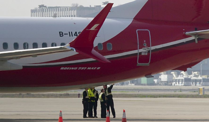 Ground crew chat near a Boeing 737 MAX 8 plane operated by Shanghai Airlines parked on tarmac at Hongqiao airport in Shanghai, China, Tuesday, March 12, 2019. U.S. aviation experts on Tuesday joined the investigation into the crash of an Ethiopian Airlines jetliner that killed 157 people, as a growing number of airlines grounded the new Boeing plane involved in the crash. (AP Photo)