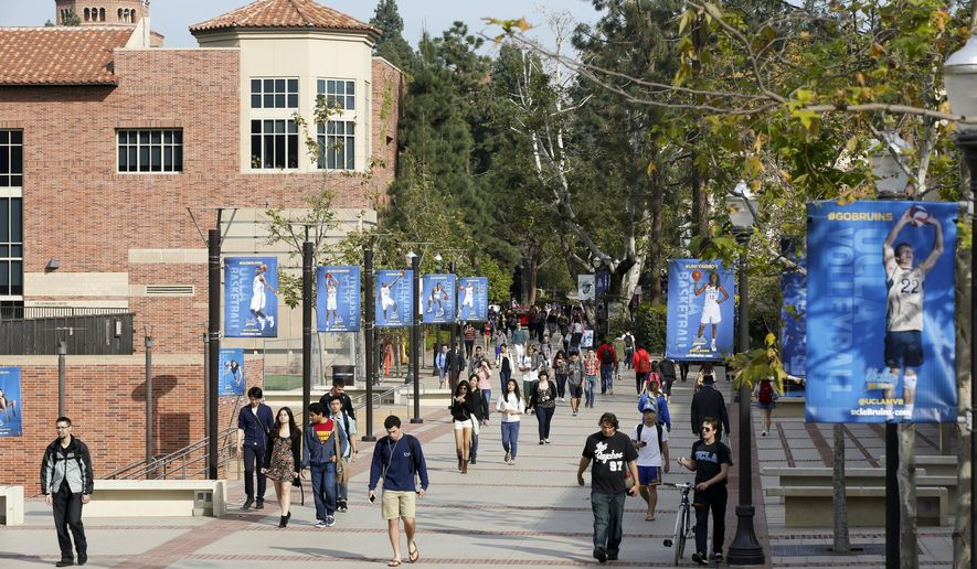 In this Feb. 26, 2015, file photo, students walk on the University of California, Los Angeles campus. Federal authorities have charged college coaches and others in a sweeping admissions bribery case in federal court. The racketeering conspiracy charges were unsealed Tuesday, March 12, 2019, against coaches at schools including UCLA, Wake Forest, Stanford, Georgetown, and the University of Southern California. (AP Photo/Damian Dovarganes, File) **FILE**