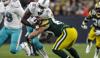 FILE - In this Nov. 11, 2018, file photo, Miami Dolphins' DeVante Parker (11) is brought down during an NFL football game against the Green Bay Packers in Green Bay, Wis. Parker has signed an incentive-laden, two-year deal worth up to $13 million that replaces a $9.4 million fifth-year option on his original contract. (AP Photo/Jeffrey Phelps, File)