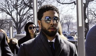 """Empire"" actor Jussie Smollett, center, arrives at Leighton Criminal Court Building for a hearing to discuss whether cameras will be allowed in the courtroom during his disorderly conduct case on Tuesday, March 12, 2019, in Chicago. A grand jury indicted Smollett last week on 16 felony counts accusing him of lying to the police about being the victim of a racist and homophobic attack by two masked men in downtown Chicago.(AP Photo/Matt Marton)"