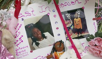 Photos adorn a large memorial to Trinity Love Jones, the 9-year-old girl whose body was found in a duffel bag along a suburban Los Angeles equestrian trail, in Hacienda Heights, Calif., Monday, March 11, 2019. Two people have been detained in connection with the case. The discovery happened last week. (AP Photo/Reed Saxon)