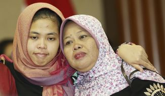 Indonesian Siti Aisyah, left, hugs her mother Benah, right, after a press conference at foreign minister office in Jakarta, Indonesia, Monday, March 11, 2019. The Indonesian woman held two years on suspicion of killing North Korean leader's half brother Kim Jong Nam was freed from custody Monday after prosecutors unexpectedly dropped the murder charge against her.(AP Photo/Achmad Ibrahim)