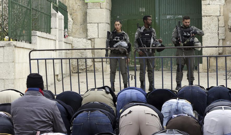 Palestinians pray outside the Old City as Israeli border police blocked the entrances to Al-Aqsa compound in Jerusalem Tuesday, March 12, 2019. Israeli police on Tuesday closed the entrances to Jerusalem's most sensitive holy site after Palestinian suspects threw a firebomb at a police station. (AP Photo/Mahmoud Illean)