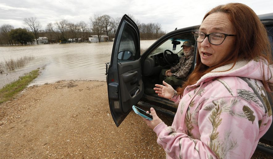 """In this Monday, March 11, 2019 photo, Peggy and her husband George Sellars sit by the """"lake"""" that was the driveway to their home, along Mississippi 16, east of Rolling Fork, Miss. The couple said the backwater flooding is the worse they have encountered and correctly concluded that water would overtop the retention levee that protected their house and three others. This week the Federal Emergency Management Agency (FEMA), the Mississippi Emergency Management Agency (MEMA), along with select local emergency management offices will be conducting joint damage assessments in response to the severe storms and flooding are impacting the state. (AP Photo/Rogelio V. Solis)"""