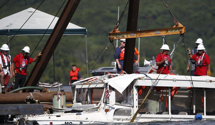 FILE - In this July 23, 2018 file photo, the duck boat that sank in Table Rock Lake in Branson, Mo., is raised. The company that owned the tourist boat that sank in a Missouri lake has reached a settlement with relatives of two brothers who were among 17 people who died in the accident. (Nathan Papes/The Springfield News-Leader via AP, File)