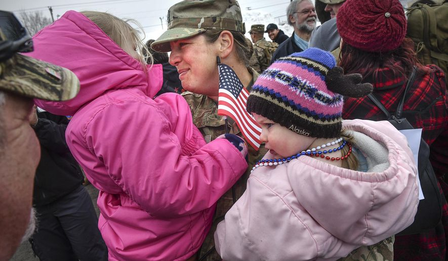 Nickole Wells hugs her daughters Nora and Amelia during a homecoming ceremony for about 160 members of the Minnesota National Guard's 851st Vertical Engineer Company Tuesday, March 12, 2019, in St. Cloud, Minn. The unit was deployed for nine months to Kuwait in support of Operation Freedom's Sentinel. During their deployment, soldiers completed construction projects in support of military units in several countries including Kuwait, Qatar, Jordan, Syria, the United Arab Emirates and Afghanistan.  (Dave Schwarz/St. Cloud Times via AP)