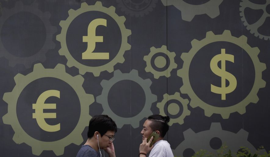 FILE- In this Aug. 6, 2018, file photo people walk by a mural displaying world currency symbols on display outside a bank in Beijing. Currency changes, wire transfer fees and limited access to financial services back home can make it hard to manage debt as an expat. (AP Photo/Andy Wong, File)