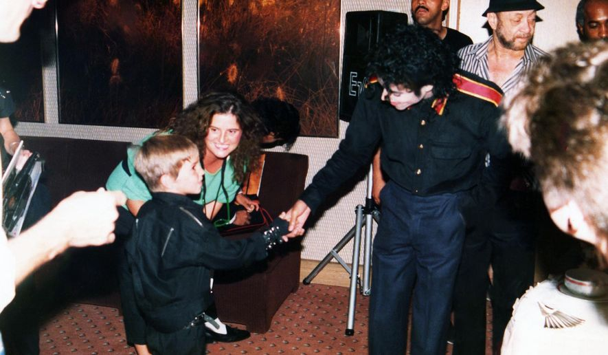"""This image released by HBO shows a young Wade Robson shaking hands with pop icon Michael Jackson in 1987, in a scene from the documentary """"Leaving Neverland."""" The unsparing documentary about Jackson and his alleged sexual abuse is already the third most-watched documentary of the past decade at the prime cable network, which takes pride in its documentary schedule. The Nielsen company said the first half of the four-hour program has been seen by 3.67 million people. (Dan Reed/HBO via AP)"""