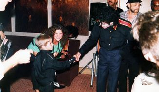 "This image released by HBO shows a young Wade Robson shaking hands with pop icon Michael Jackson in 1987, in a scene from the documentary ""Leaving Neverland."" The unsparing documentary about Jackson and his alleged sexual abuse is already the third most-watched documentary of the past decade at the prime cable network, which takes pride in its documentary schedule. The Nielsen company said the first half of the four-hour program has been seen by 3.67 million people. (Dan Reed/HBO via AP)"