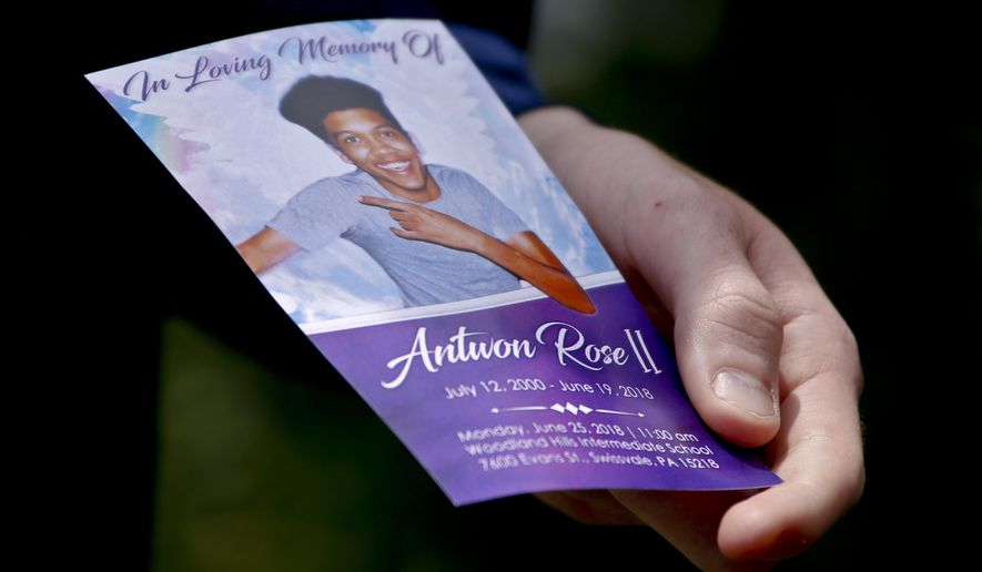 File-In this file photo from June 25, 2018, Kyle Fogarty shows a memorial card of Antwon Rose II after the funeral in Swissvale, Pa. Rose was fatally shot by a police officer seconds after he fled a traffic stop June 19, 2018 in the suburb of East Pittsburgh. The jury selection begins Tuesday in Harrisburg for the trial of former officer Michael Rosfeld, who is charged with criminal homicide. A judge ruled a jury from outside the Pittsburgh area is needed because of widespread publicity about the case. The jurors will be taken to Allegheny County for the trial next week. (AP Photo/Keith Srakocic, File)