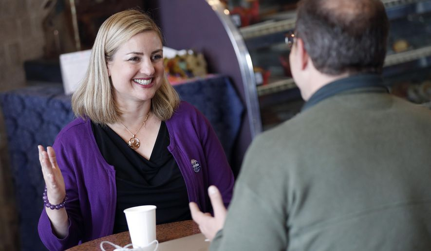 Phoenix mayoral candidate Kate Gallego, right, talks with voters at a coffee shop, Tuesday, March 12, 2019 in Phoenix. Voters in Phoenix will go to the polls Tuesday to choose the city's next mayor. Gallego and Daniel Valenzuela were forced in to a runoff after neither had enough votes to win the general election in November. (AP Photo/Matt York)