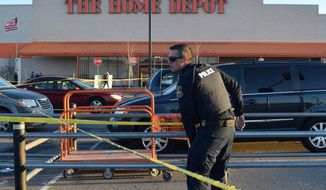 In a Monday, March 11, 2019 photo, a St. Clair Shores police officer places caution tape in the parking lot at the Home Depot in Roseville, Mich., where authorities say police shot and wounded a man who pulled a handgun at the home improvement store. A 22-year-old man allegedly pulled a gun inside the store and then they say the man raised the gun at them outside and was shot. The man was taken to a hospital and was reportedly in stable condition. (Mitch Hosts/The Macomb Daily via AP)