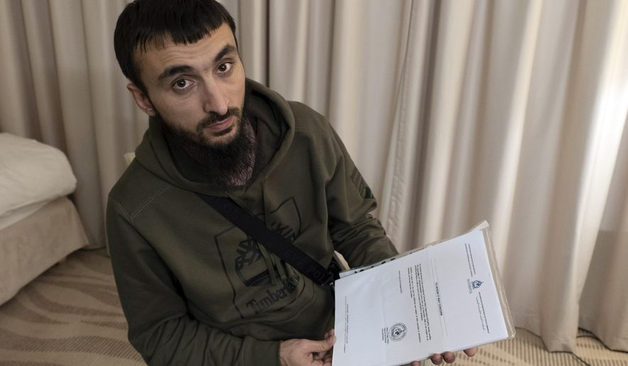 FILE - In this file photo taken on Wednesday, Nov. 14, 2018, Tumso Abdurakhmanov, the 32-year-old Chechen video blogger, and critic of the Chechen ruler Ramzan Kadyrov, holds a letter from Interpol during an interview with The Associated Press somewhere in Poland.  The speaker of Chechnya's parliament Magomedov Daudov, says he has a blood feud against the popular Chechen blogger who has fled Russia and is believed to be seeking asylum in Poland. (AP Photo/Francesca Ebel, File)