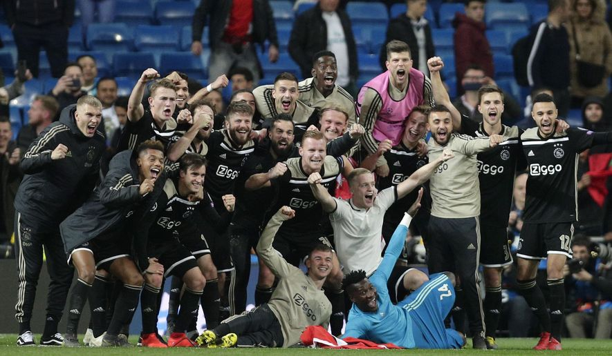 Ajax players celebrate after wining the game, at the end of the Champions League soccer match between Real Madrid and Ajax at the Santiago Bernabeu stadium in Madrid, Spain, Tuesday, March 5, 2019. (AP Photo/Manu Fernandez)
