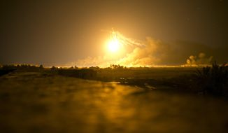An illumination round lights up the battlefield as U.S.-backed Syrian Democratic Forces (SDF) fire on Islamic State militant positions in Baghouz, Syria, Monday, March 11, 2019. (AP Photo/Maya Alleruzzo)