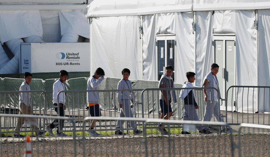 FILE - In this Feb.19, 2019 file photo, children line up to enter a tent at the Homestead Temporary Shelter for Unaccompanied Children in Homestead, Fla. U.S. Sen. Jeff Merkley said Monday, March 11, 2019 that he toured the Florida facility and found children are being held there for too long in a restrictive environment. (AP Photo/Wilfredo Lee, File)