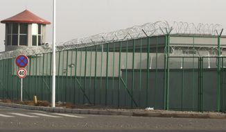 """FILE - In this Monday, Dec. 3, 2018, file photo, a guard tower and barbed wire fences surround an internment facility in the Kunshan Industrial Park in Artux in western China's Xinjiang region. A U.S. envoy on religion has described China's internment of an estimated 1 million Muslims as a """"horrific situation."""" Ambassador-at-large Sam Brownback called for an independent investigation into the detentions and the release of those being held. (AP Photo/Ng Han Guan/file)"""