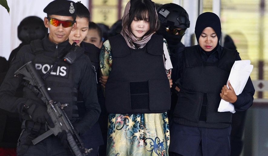 FILE - In this April 5, 2018, file photo, Vietnamese Doan Thi Huong, center, is escorted by police as she leaves after a court hearing at the Shah Alam High Court in Shah Alam, Malaysia. Vietnam is urging Malaysia to release the second woman accused of killing the estranged half brother of North Korea's leader. Foreign Minister Pham Binh Minh made the plea in a phone call Tuesday, March 12, 2019, with his counterpart, Saifuddin Abdullah. A statement posted on the ministry's website said Minh requested the Malaysian court conduct a fair trial and free Huong. (AP Photo/Sadiq Asyraf, File)