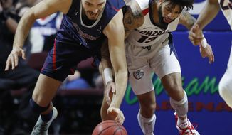 St. Mary's Jock Perry, left, and Gonzaga's Josh Perkins scramble for the ball during the first half of an NCAA college basketball game for the West Coast Conference men's tournament title, Tuesday, March 12, 2019, in Las Vegas. (AP Photo/John Locher)
