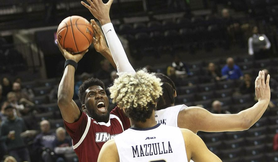 Massachusetts' Jonathan Laurent, left, shoots over George Washington defenders during the first half of an NCAA college basketball game in the Atlantic 10 conference tournament, Wednesday, March 13, 2019, in New York. (J. Anthony Roberts/The Republican via AP)