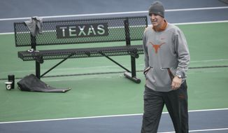 Texas' head coach Michael Center, in his 18th season, surveys the courts before the matches with UTSA., Jan. 19, 2018 in Austin, Texas. The Inaugural Matches at the new Texas Tennis Center are being held Friday afternoon January 19-21, 2018, as the University of Texas Men's team opens against UTSA. (Ralph Barrera/Austin American-Statesman via AP)