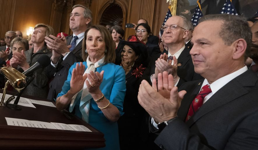 Speaker of the House Nancy Pelosi, D-Calif., flanked by Sen. Jeff Merkley, D-Ore., left, and Rep. David Cicilline, D-R.I., right, applauds with fellow Democrats as they announce the introduction of The Equality Act, a comprehensive nondiscrimination bill for LGBT rights, at the Capitol in Washington, Wednesday, March 13, 2019. (AP Photo/J. Scott Applewhite)