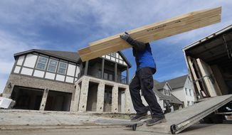 In this Feb. 20, 2019, photo a worker carries interior doors to install in a just completed new home in north Dallas. On Wednesday, March 13, the Commerce Department reports on U.S. construction spending in January.  (AP Photo/LM Otero) **FILE**