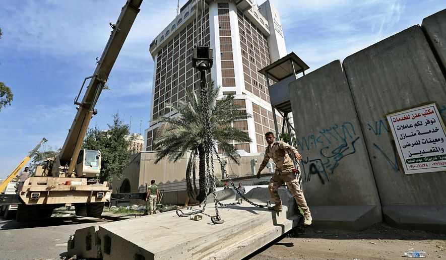 Iraqi security forces remove concrete blast walls in Abu Nawas street in central Baghdad, Iraq, Wednesday, March 13, 2019. (AP Photo/Hadi Mizban)