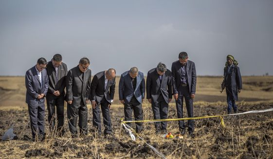 Officials from the Aviation Industry Corporation of China (AVIC) pray next to an offering of fruit, bread rolls, and a plastic container of Ethiopian Injera, a fermented sourdough flatbread, placed next to incense sticks, at the scene where the Ethiopian Airlines Boeing 737 Max 8 crashed shortly after takeoff on Sunday killing all 157 on board, near Bishoftu, or Debre Zeit, south of Addis Ababa, in Ethiopia Tuesday, March 12, 2019. Ethiopian Airlines had issued no new updates on the crash as of late afternoon Tuesday as families around the world waited for answers, while a global team of investigators began picking through the rural crash site. (AP Photo/Mulugeta Ayene) **FILE**