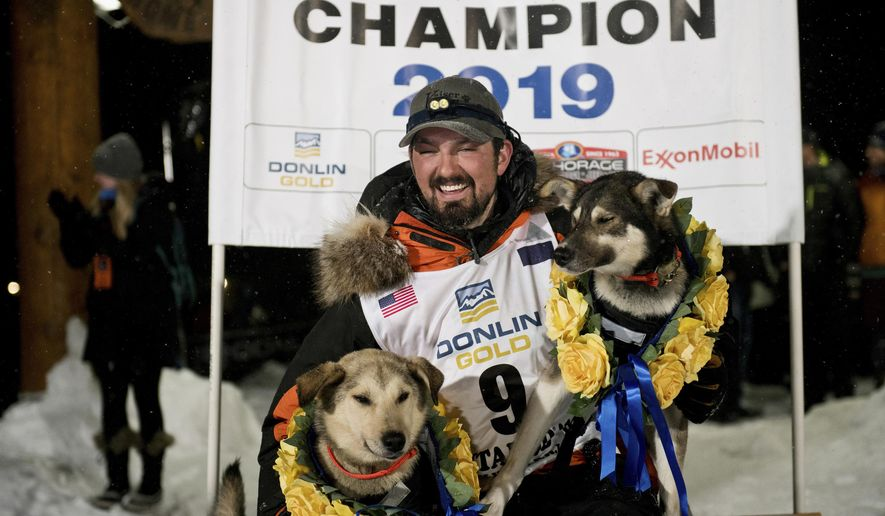Peter Kaiser (9) poses with his lead dogs, Morrow, left, and Lucy., Wednesday, March 13, 2019, in Nome, Alaska, after winning the Iditarod Trail Sled Dog Race. It's the first Iditarod victory for Kaiser in his 10th attempt. (Marc Lester/Anchorage Daily News via AP)