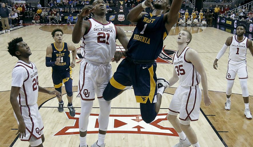West Virginia's Derek Culver (1) gets past Oklahoma's Kristian Doolittle (21) to put up a shot during the first half of an NCAA college basketball game in the Big 12 men's tournament Wednesday, March 13, 2019, in Kansas City, Mo. (AP Photo/Charlie Riedel)