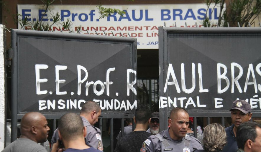 Police officers guard the entrance of the Raul Brasil State School in Suzano, Brazil, Wednesday, March 13, 2019. The state government of Sao Paulo said two teenagers, armed with guns and wearing hoods, entered the school and began shooting at students. They then killed themselves, according to the statement. (Mauricio Sumiya/Futura Press via AP)