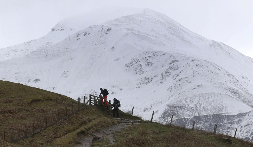 """Hill walkers make their way along the Ben Nevis mountain path in Scotland, Wednesday March 13, 2019. A young climber is being treated for serious injuries after an avalanche on the UK's highest mountain """"wiped out"""" a climbing party on Tuesday, killing some of them and triggering a search and recovery operation in """"brutal conditions"""", a rescuer said. (Andrew Milligan/PA via AP)"""