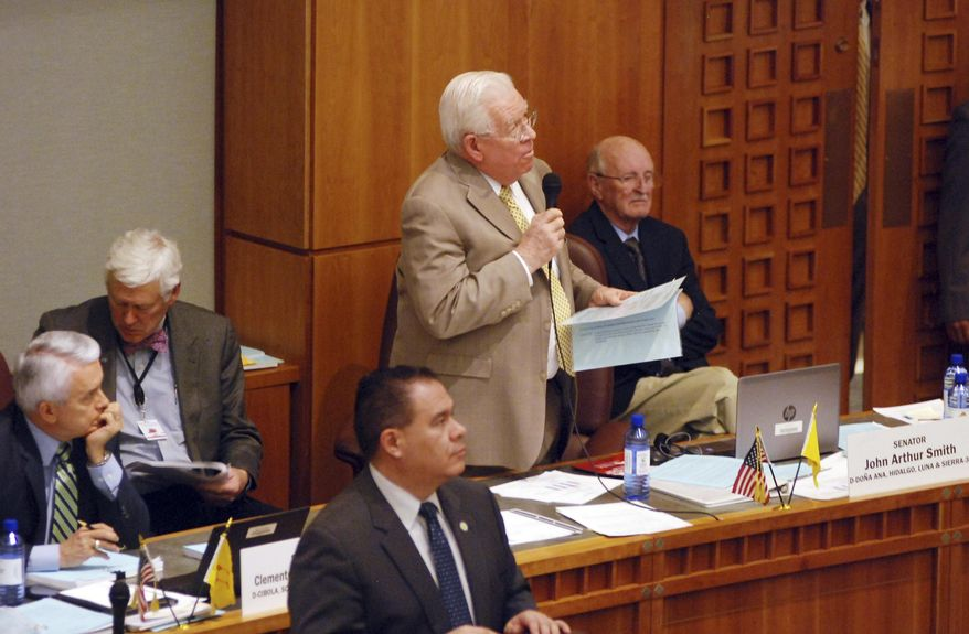 Democratic Sen. John Arthur Smith, of Deming, at center with microphone, guides a $700 million annual spending increase from New Mexico's general fund through approval by the state Senate on Wednesday, March 13, 2019, in Santa Fe, N.M. The House and Senate are moving closer to agreement that would increase spending on public education by nearly half a billion dollars and channel a windfall in tax income toward infrastructure and economic stimulus. (AP Photo/Morgan Lee)