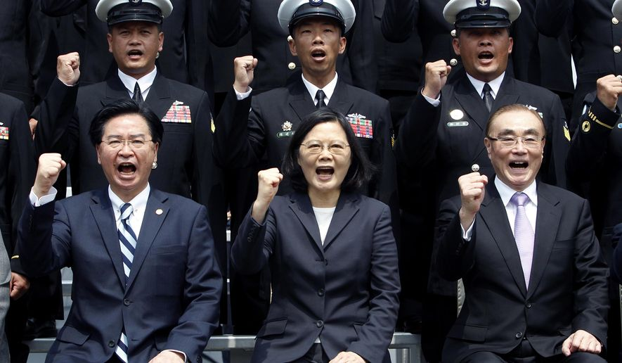 "FILE - In this March 21, 2017, file photo, Taiwan's President Tsai Ing-wen, center, along with Defense Minister Feng Shih-kuan, right, and Secretary-General of National Security Council Joseph Wu, left, cheer with navy officers during a visit to Zuoying Naval base in Kaohsiung, southern Taiwan. China says attempts by Taiwan's government to block its goal of bringing the self-governing island under Beijing's control are like ""stretching out an arm to block a car."" The new rhetorical broadside was launched late Tuesday, March 12, 2019 against Taiwanese President Tsai following her announcement of guidelines to counter China's ""one country, two systems"" framework for political unification with the island. (AP Photo/Chiang Ying-ying, File)"