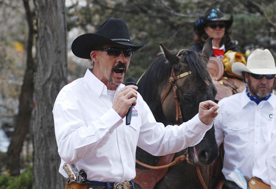 Cibola County Sheriff Tony Mace rallies protesters against gun control legislation at a gathering outside the New Mexico state Capitol, on Tuesday, March 12, 2019. Advocates for gun rights in New Mexico including rural ranchers joined with a interstate group called Cowboys for Trump at a protest against Democrat-sponsored gun control legislation and a bill that removes the state's dormant ban on abortion. Democratic New Mexico Gov. Michelle Lujan Grisham last week signed a bill to expand background checks on private gun sales. (AP Photo/Morgan Lee)