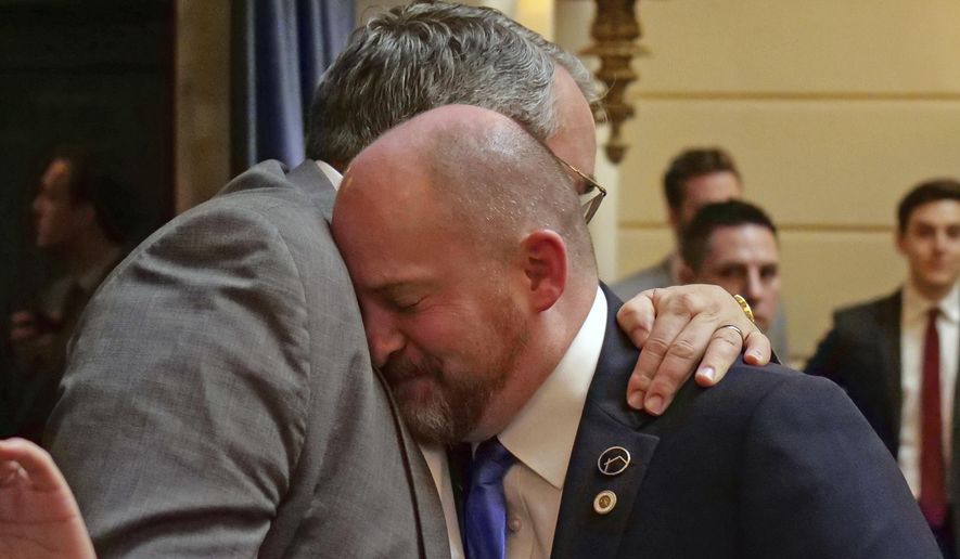 Sen. Daniel Thatcher, foreground, R-West Valley City, receives a hug from Rep. Lee Perry, R-Perry, on the Senate floor following a vote Wednesday, March 13, 2019, in Salt Lake City. A once-stalled measure to strengthen Utah's hate crime law has passed the Legislature and is poised to become law. The Utah Senate cast the final vote to pass the measure, and Republican Gov. Gary Herbert said he's looking forward to signing it. (AP Photo/Rick Bowmer)