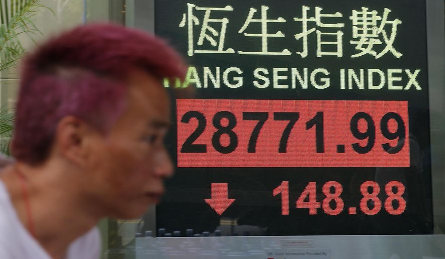 A man walks past an electronic board showing Hong Kong share index outside a bank in Hong Kong, Wednesday, March 13, 2019. Asian shares were lower Wednesday amid continuing global uncertainties that weighed on stocks as some traders took profits from a rally earlier in the week. (AP Photo/Kin Cheung)