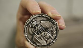This Wednesday, March 13, 2019. photo shows a coin emblazoned with the face of Nikki Haley, President Donald Trump's former ambassador to the United Nations, to commemorate her defense of Israel in the United Nations, in Jerusalem. The Sanhedrin, a Jewish group that says it aims to restore the Jewish Temple in Jerusalem, is one of three groups behind the coin. (AP Photo/Dusan Vranic)
