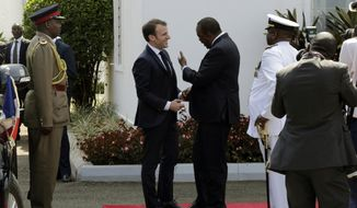 France's President Emmanuel Macron, right, meets with Kenya's President Uhuru Kenyatta on his arrival at State House in Nairobi, Kenya Wednesday, March 13, 2019. Macron is visiting Kenya Wednesday, after stops in Ethiopia and Djibouti on Tuesday, as part of his latest Africa visit aimed at shoring up military and economic ties in an increasingly strategic region. (AP Photo/Khalil Senosi)