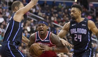 Washington Wizards guard Bradley Beal, center, drives between Orlando Magic guard Evan Fournier, from France, and center Khem Birch during the second half of an NBA basketball game Wednesday, March 13, 2019, in Washington. The Wizards won 100-90. (AP Photo/Alex Brandon)