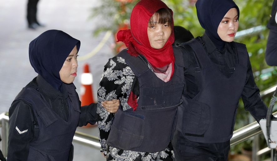 Vietnamese Doan Thi Huong, center, is escorted by police as she arrives at Shah Alam High Court in Shah Alam, Malaysia, Thursday, March 14, 2019. Vietnam has urged Malaysia to release the second woman accused of killing the estranged half brother of North Korea's leader after her co-defendant was unexpectedly set free this week.  (AP Photo/Vincent Thian)