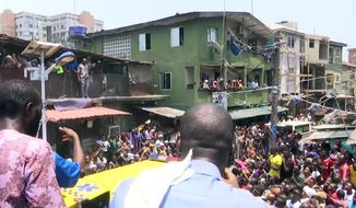 In this image taken from video rescue workers and emergency teams work at the scene of a building collapse in Lagos, Nigeria, Wednesday March 13, 2019. A three-story building has collapsed in Lagos, and rescuers rush to pull out scores of children thought to be inside. There was no immediate official word on numbers of casualties. (AP Photo)