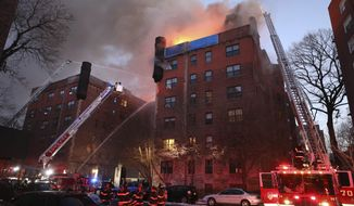 Flames leap from the roof as Yonkers firefighters battle a large fire in a six story apartment building, Tuesday, March 12, 2019, in Yonkers, N.Y. (Mark Vergari/The Journal News via AP)