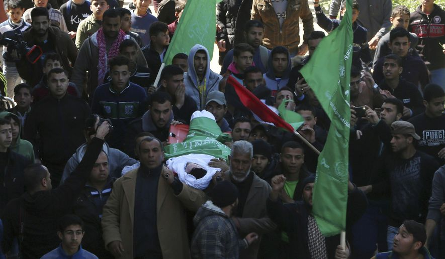 Mourners carry the body of Saif Abu Zaied, 15, during his funeral though the streets of Gaza City, Thursday, March 7, 2019. Gaza's Health Ministry said Abu Zaied died from Israeli gunfire during nighttime skirmishes along the Gaza-Israel frontier last night. (AP Photo/Adel Hana)