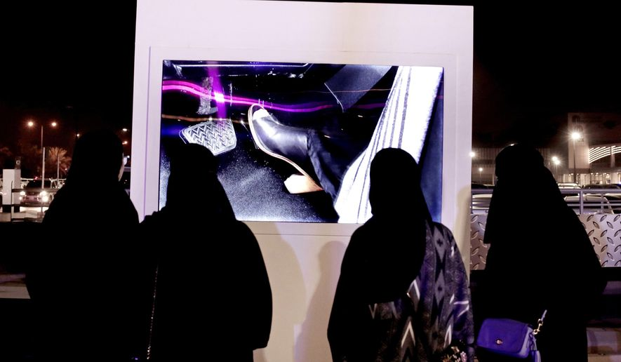FILE - In this June 22, 2018 file photo, women watch a video about driving at a road safety event for female drivers launched at the Riyadh Park Mall in Saudi Arabia. Women's rights activists in Saudi Arabia appeared in a closed-door court hearing on unknown charges, Wednesday, March 13, 2019, after being detained in a crackdown last year, making their first appearance before a judge in the internationally criticized case. (AP Photo/Nariman El-Mofty, File)